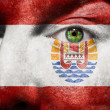 Royalty-Free Stock Photo: Flag painted on face with green eye to show French Polynesia support