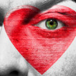 Red heart painted on face with black heart pupil — Stock Photo