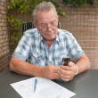 Senior searching in his mobile phone — Stock Photo