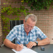 Senior signing a legal document - Stock Photo