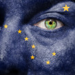 Stock Photo: Flag painted on face with green eye to show Alaska support