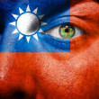 Flag painted on face with green eye to show Taiwan support - Stock Photo