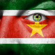 Flag painted on face with green eye to show Suriname support - Stock Photo