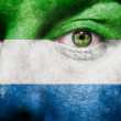 Flag painted on face with green eye to show Sierra Leone support - Stock Photo