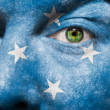 Flag painted on face with green eye to show Micronesia support — Stock Photo
