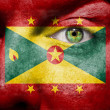 Royalty-Free Stock Photo: Flag painted on face with green eye to show Grenada support