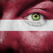 Flag painted on face with green eye to show Latvia support - Stock Photo