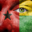 Flag painted on face with green eye to show Guinea Bissau suppor — Stock Photo