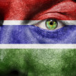 Flag painted on face with green eye to show Gambia support - Stock Photo