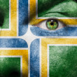 Flag painted on face with green eye to show Portland support - Stock Photo
