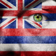 Flag painted on face with green eye to show Hawaii support - Stock Photo