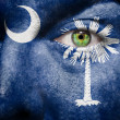 Flag painted on face with green eye to show South Carolina suppo - Stock Photo