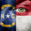 Flag painted on face with green eye to show North Carolina suppo - Stock Photo