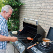 Retired dutch senior man grilling hamburgers — Stock Photo