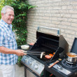 Retired dutch senior man grilling meat — Stock Photo