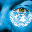 Royalty-Free Stock Photo: Flag painted on face with green eye to show UN support