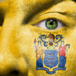 Flag painted on face with green eye to show New Jersey support — Stock Photo