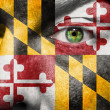 Flag painted on face with green eye to show Maryland support - Stock Photo