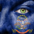 Flag painted on face with green eye to show North Dakota support — Stock Photo #15713145