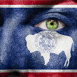 Flag painted on face with green eye to show Wyoming support — Stock Photo