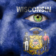 Flag painted on face with green eye to show Wisconsin support — Stock Photo