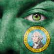 Flag painted on face with green eye to show Washington support — Stock Photo