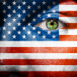 Flag painted on face with green eye to show USA support — Stock Photo