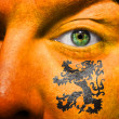 Dutch Lion painted on orange face - Stock Photo