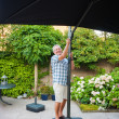 Senior man setting up beach parasol — Stock Photo