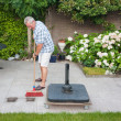 Senior man sweeping back garden — Stock Photo