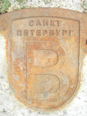 Old rusted manhole cover with the name of the city — Foto Stock