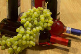 Bottles of wine and grapes. — Stock Photo