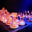 ストック写真: Glass chess on chessboard lit by blue and orange light