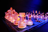 Glass chess on a chessboard lit by a blue and orange light — Stock Photo