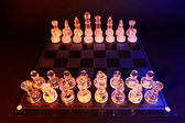 Glass chess on a chessboard lit by a blue and orange light — Photo