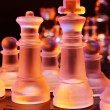 Stockfoto: Glass chess on chessboard lit by blue and orange light