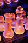 Glas Schaken op een schaakbord verlicht door een licht blauwe en oranje — Stockfoto