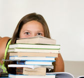 Teen female student peeking over book stack — Stock Photo