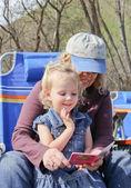 Grandma reading to toddler in park — Stock Photo