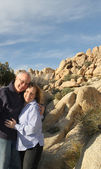 Senior couple standing with desert rock formations — Stock Photo