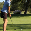Female teen golfer putting home — Stock fotografie