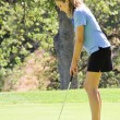 Female teen golfer putting on green — 图库照片