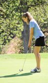 Female teen golfer putting on green — ストック写真