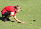 Young male golfer lining up putt — Stock Photo