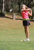 Female teen golfer teeing off — Stock Photo
