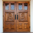 Hand-carved Jesus on wooden church doors — Stock Photo #39876323