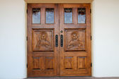 Hand-carved Jesus on wooden church doors — Stock Photo