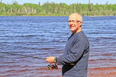 Retired Senior Male lake fishing — Stock Photo