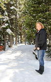 Senior female walking in snowy woods — Stock Photo