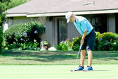 Male teen golfer preparing to putt — Photo